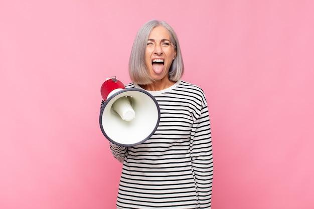 Kobieta w średnim wieku o wesołej, beztroskiej, buntowniczej postawie, żartującej i wystawiającej język, bawiąca się megafonem