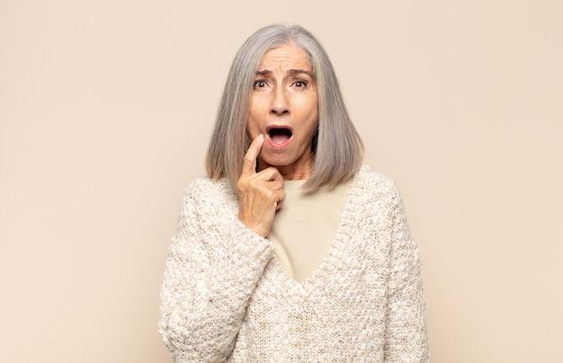 Kobieta w średnim wieku o wyglądzie zdziwionym, nerwowym, zmartwionym lub przestraszonym, spoglądająca w bok w stronę przestrzeni kopii