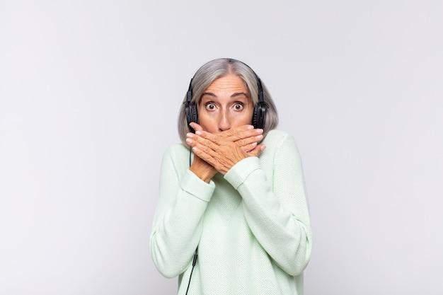 Kobieta w średnim wieku obejmujące usta rękami z wstrząśnięciem na białym tle