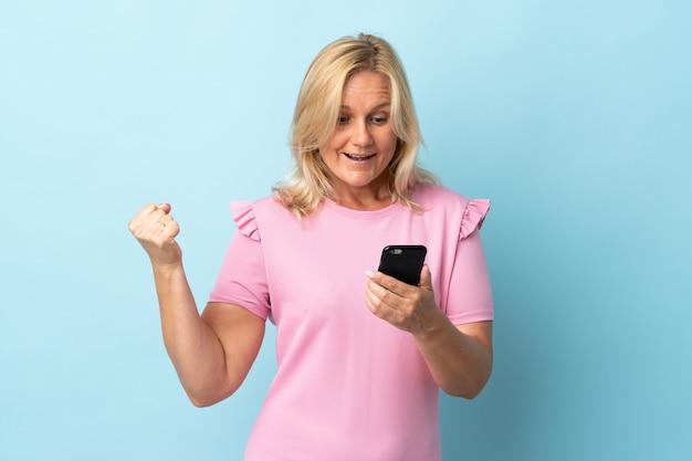 Kobieta w średnim wieku odizolowana na niebieskiej ścianie zaskoczona i wysyłająca wiadomość