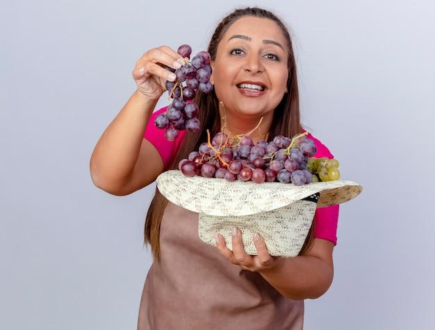 Kobieta w średnim wieku ogrodniczka w fartuchu trzymająca kapelusz pełen winogron z uśmiechem na twarzy