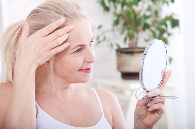 Kobieta w średnim wieku, patrząc na zmarszczki w lustrze. selektywna ostrość