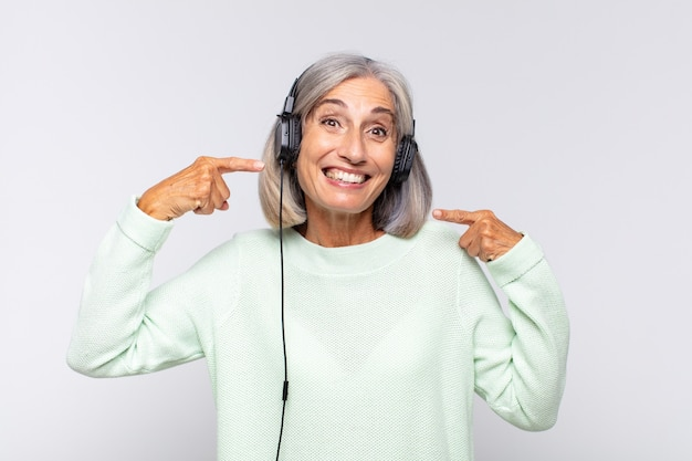 Kobieta w średnim wieku, pewnie uśmiechnięta, wskazująca na swój szeroki uśmiech, pozytywne, zrelaksowane, zadowolone nastawienie