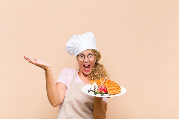 Kobieta w średnim wieku piekarz gotowania gofrów
