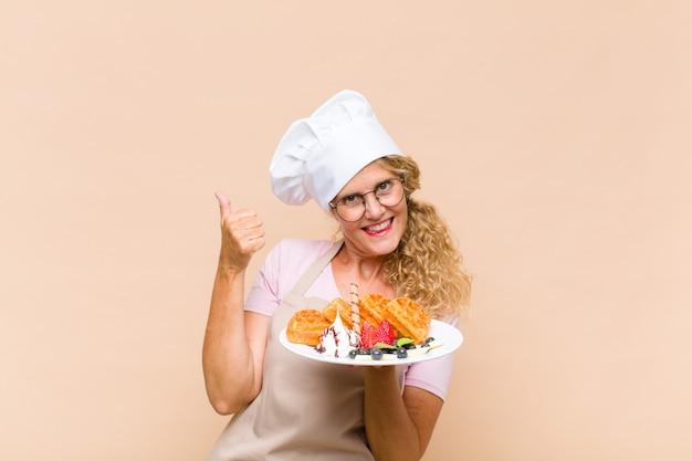 Kobieta w średnim wieku piekarz gotuje gofry