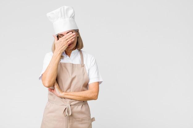Kobieta w średnim wieku, piekarz wyglądająca na zestresowaną, zawstydzoną lub zdenerwowaną, z bólem głowy, zakrywającą twarz dłonią na płaskiej ścianie
