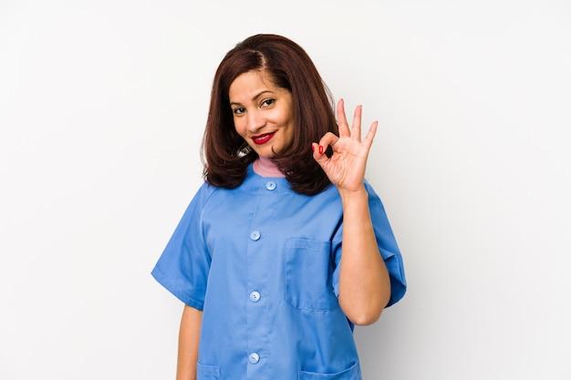 Kobieta w średnim wieku pielęgniarka łacińska na białym tle che wspaniały i pewny siebie pokazuje gest.
