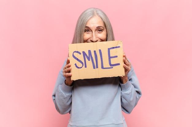 Kobieta w średnim wieku posiadająca znak z uśmiechem tekst