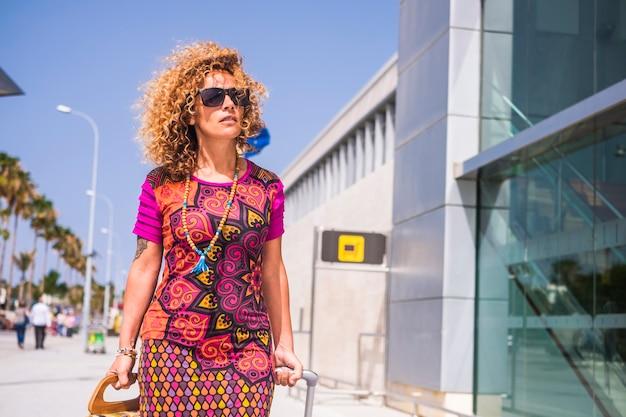 Kobieta w średnim wieku poza lotniskiem przy przylocie lub odlocie spacer z torbą na kółkach i torebką w poszukiwaniu informacji