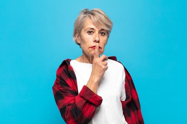 """Kobieta w średnim wieku prosząca o ciszę i spokój, gestykulująca palcem przed ustami, mówiąca """"cii"""" lub dochować tajemnicy"""