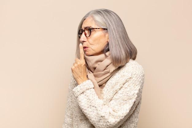 Kobieta w średnim wieku prosząca o ciszę i spokój, gestykulująca palcem przed ustami, mówiąca cii lub zachowując tajemnicę