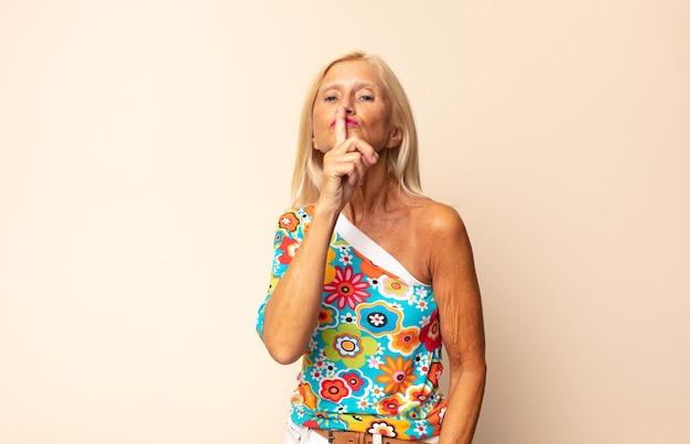Kobieta w średnim wieku prosząca o ciszę i spokój, wskazująca palcem przed ustami, mówiąca ciii lub dochowując tajemnicy