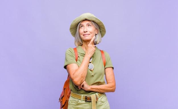 Kobieta w średnim wieku radośnie się uśmiecha i marzy lub wątpi, patrząc w bok