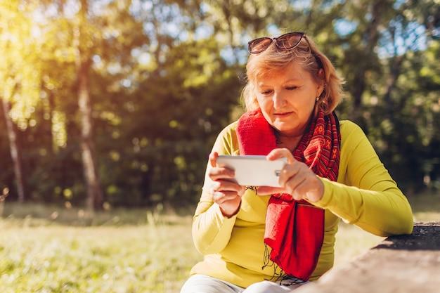 Kobieta w średnim wieku relaks przy użyciu telefonu na zewnątrz. stylowa starsza pani oglądając wideo na smartfonie w jesiennym lesie.