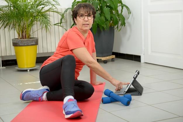 Kobieta w średnim wieku robi fitness ćwiczenia z tabletem