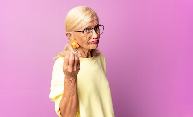 Kobieta w średnim wieku robi gest capice lub pieniądze