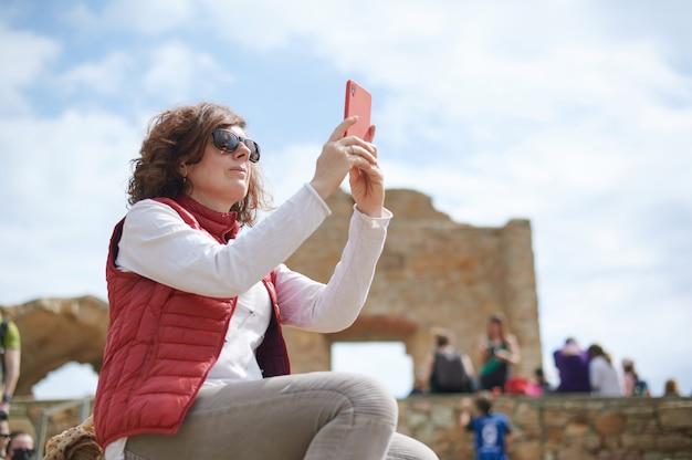 Kobieta w średnim wieku robi zdjęcie swoim smartfonem w ruinach archeologicznych