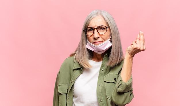 Kobieta w średnim wieku robiąca kaprysy lub gesty pieniężne, mówiąc ci, żebyś spłacił swoje długi!