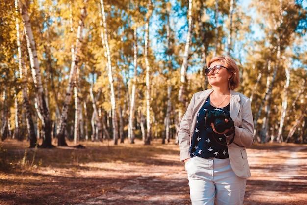 Kobieta w średnim wieku robienia zdjęć za pomocą aparatu w jesiennym lesie. stylowa starsza kobieta spacerująca i ciesząca się hobbystycznym robieniem zdjęć