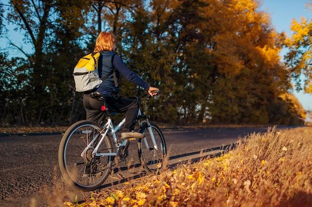 Kobieta w średnim wieku rowerzysta jazda w jesień pole o zachodzie słońca. starsza sportsmenka podziwiająca widok i odpoczywająca.