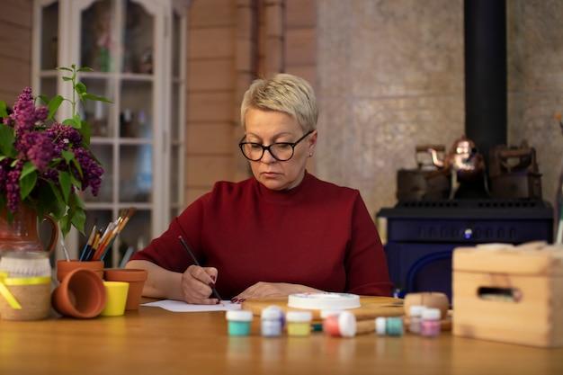 Kobieta w średnim wieku rysuje ołówkiem w przytulnym wiejskim domu z kominkiem