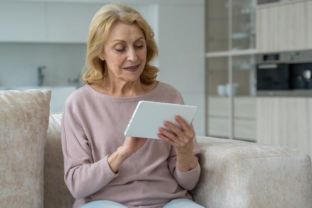 Kobieta w średnim wieku siedzi na kanapie w salonie bawi się z tabletem przy użyciu koncepcji