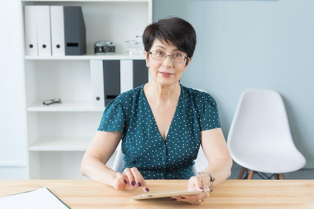 Kobieta w średnim wieku siedzi przy stole i korzysta z tabletu