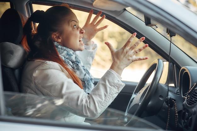 Kobieta w średnim wieku siedzi w samochodzie i narzeka na sytuację na drodze