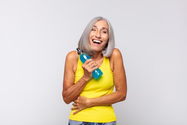 Kobieta w średnim wieku śmiejąca się głośno z jakiegoś przezabawnego żartu, czująca się szczęśliwa i wesoła, dobrze się bawiąca. koncepcja fitness