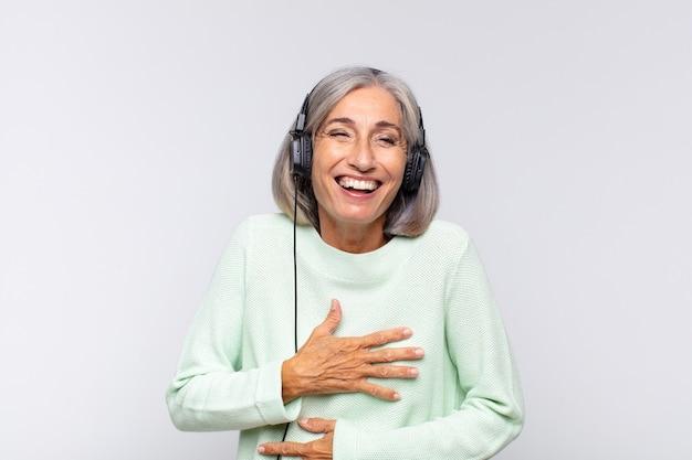 Kobieta w średnim wieku śmiejąca się głośno z jakiegoś przezabawnego żartu, czująca się szczęśliwa i wesoła, dobrze się bawiąca. koncepcja muzyki