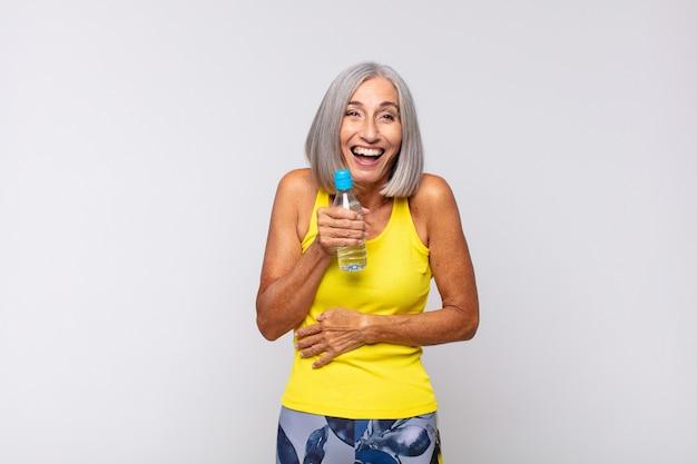 Kobieta w średnim wieku śmiejąca się głośno z jakiegoś zabawnego żartu na białym tle