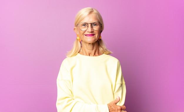 Kobieta w średnim wieku śmiejąca się nieśmiało i wesoło