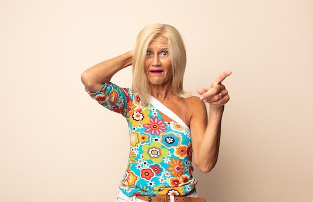 Kobieta w średnim wieku śmiejąca się, wyglądająca na szczęśliwą, pozytywną i zaskoczoną, realizująca świetny pomysł wskazujący na boczną przestrzeń kopii