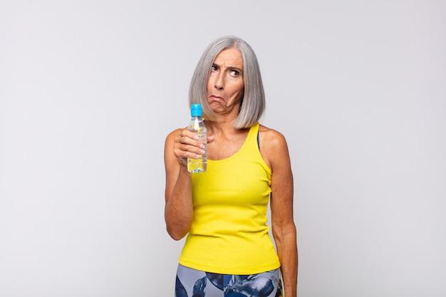 Kobieta w średnim wieku smutna i jęcząca z nieszczęśliwym spojrzeniem, płacząca z negatywnym i sfrustrowanym nastawieniem