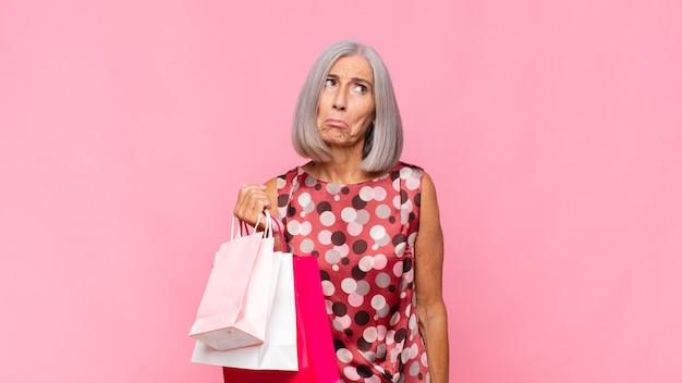 Kobieta w średnim wieku, smutna i jęcząca z nieszczęśliwym spojrzeniem, płacze z negatywnym i sfrustrowanym nastawieniem do toreb na zakupy