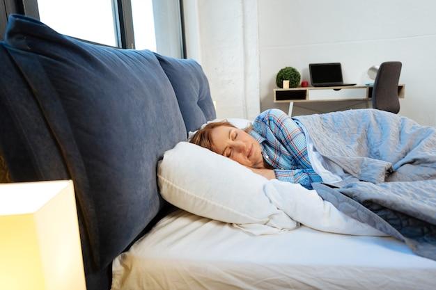 Kobieta w średnim wieku śpi. spokojna, przystojna kobieta ubrana w niebieską piżamę w kratkę podczas snu w sypialni