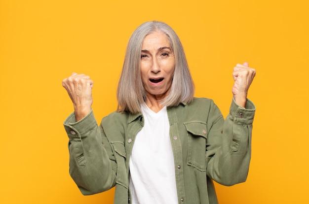 Kobieta w średnim wieku świętująca niewiarygodny sukces jak zwycięzca, wyglądająca na podekscytowaną i szczęśliwą, mówiąc: weź to!