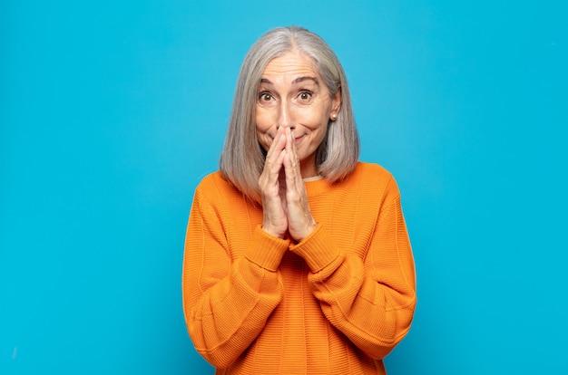 Kobieta w średnim wieku szczęśliwa i podekscytowana, zaskoczona i zdumiona zakrywająca usta rękami, chichocząca z uroczym wyrazem twarzy