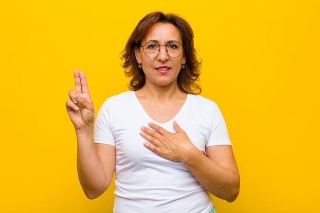 Kobieta w średnim wieku, szczęśliwa, pewna siebie i godna zaufania, uśmiechnięta i pokazująca znak zwycięstwa, z pozytywnym nastawieniem do żółtej ściany