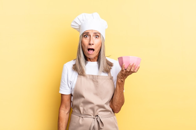 """Kobieta w średnim wieku, szefowa kuchni, wyglądająca na bardzo zszokowaną lub zaskoczoną, patrząca z otwartymi ustami, mówiąca """"wow"""" i trzymająca pusty garnek"""