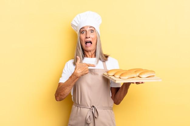 Kobieta w średnim wieku, szefowa kuchni, zszokowana i zaskoczona, z szeroko otwartymi ustami, wskazując na siebie i trzymająca tacę z chlebem