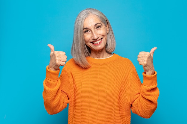 Kobieta w średnim wieku, szeroko uśmiechnięta, szczęśliwa, pozytywna, pewna siebie i odnosząca sukcesy, z dwoma kciukami do góry