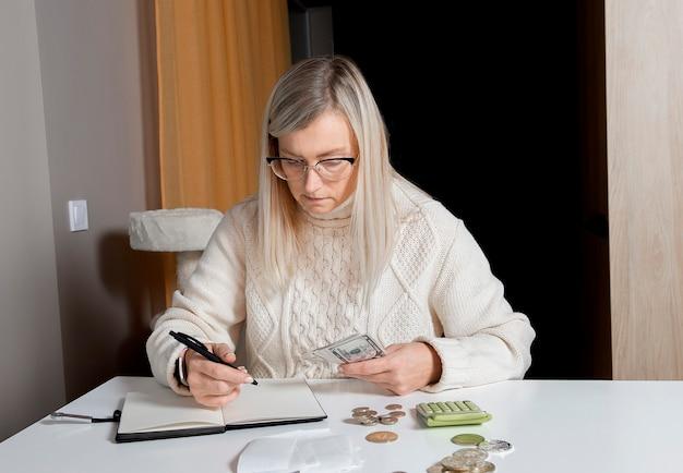 Kobieta w średnim wieku trzyma w rękach pieniądze banknotów dolara i dokonuje wpisu w notatniku planisty