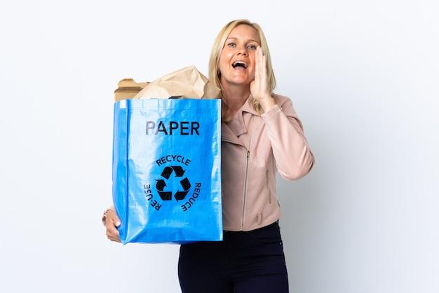 Kobieta w średnim wieku trzyma worek recyklingu pełnego papieru do recyklingu na białym krzycząc z szeroko otwartymi ustami