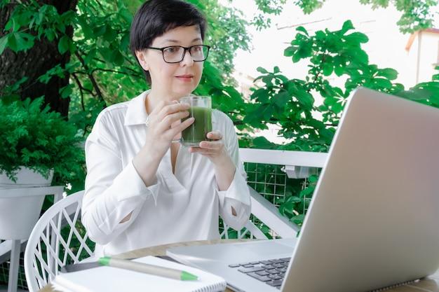 Kobieta w średnim wieku trzymać kubek zielony matcha herbaty szkła