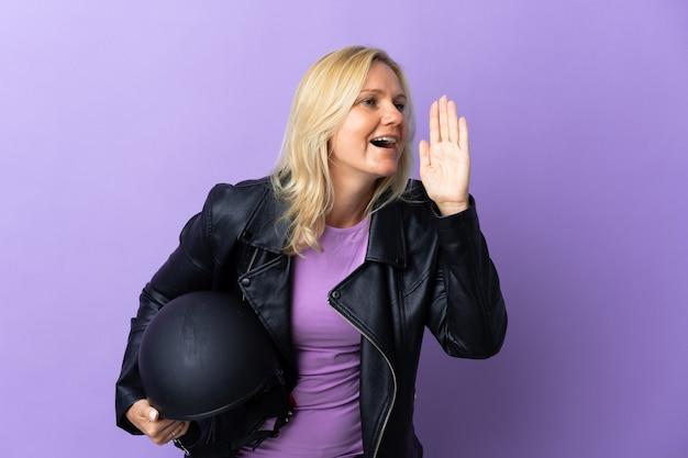 Kobieta w średnim wieku, trzymając kask motocyklowy na fioletowym tle, krzycząc z szeroko otwartymi ustami