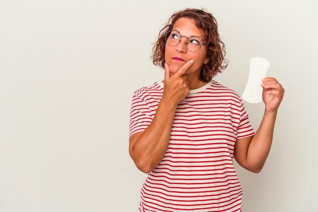 Kobieta w średnim wieku trzymając kompres na białym tle patrząc w bok z wyrazem wątpliwości i sceptyczny.