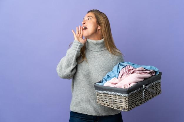 Kobieta w średnim wieku trzymając kosz z ubraniami na fioletowym tle, krzycząc z szeroko otwartymi ustami