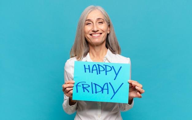 Kobieta w średnim wieku trzymająca kartkę papieru z tekstem: happy friday