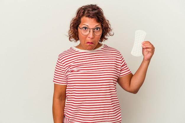 Kobieta w średnim wieku trzymająca kompres na białym tle wzrusza ramionami i otwiera oczy zdezorientowana.